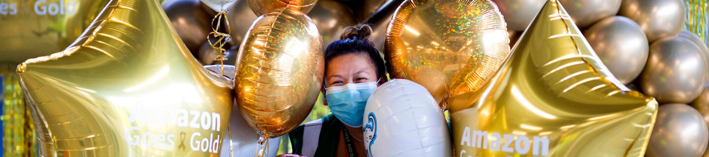A masked woman holds a bunch of gold balloons.